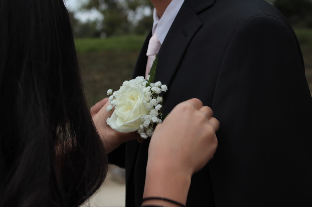 Freshman Kaylee Seo pins a boutonniere on her formal date, Bryan Choi.