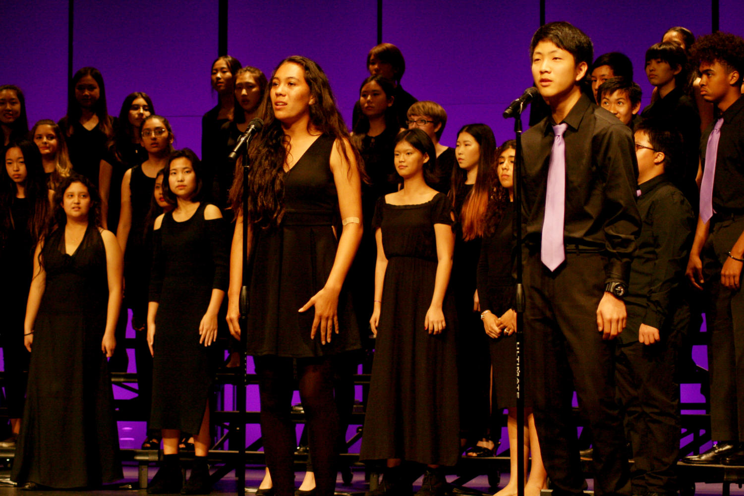 """Sophomore Kylie Palacio and freshman Justin Kim perform the second solo of """"Oye"""", the last song of the festival, in Spanish. Though there was a mike issue, both singers pushed through and kept their voices strong."""