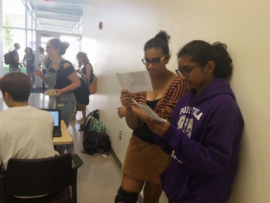 Freshmen+Zara+Shirwany+and+Naria+Alam+intently+study+their+lines+outside+the+theater+doors+as+they+wait+for+their+auditions.+