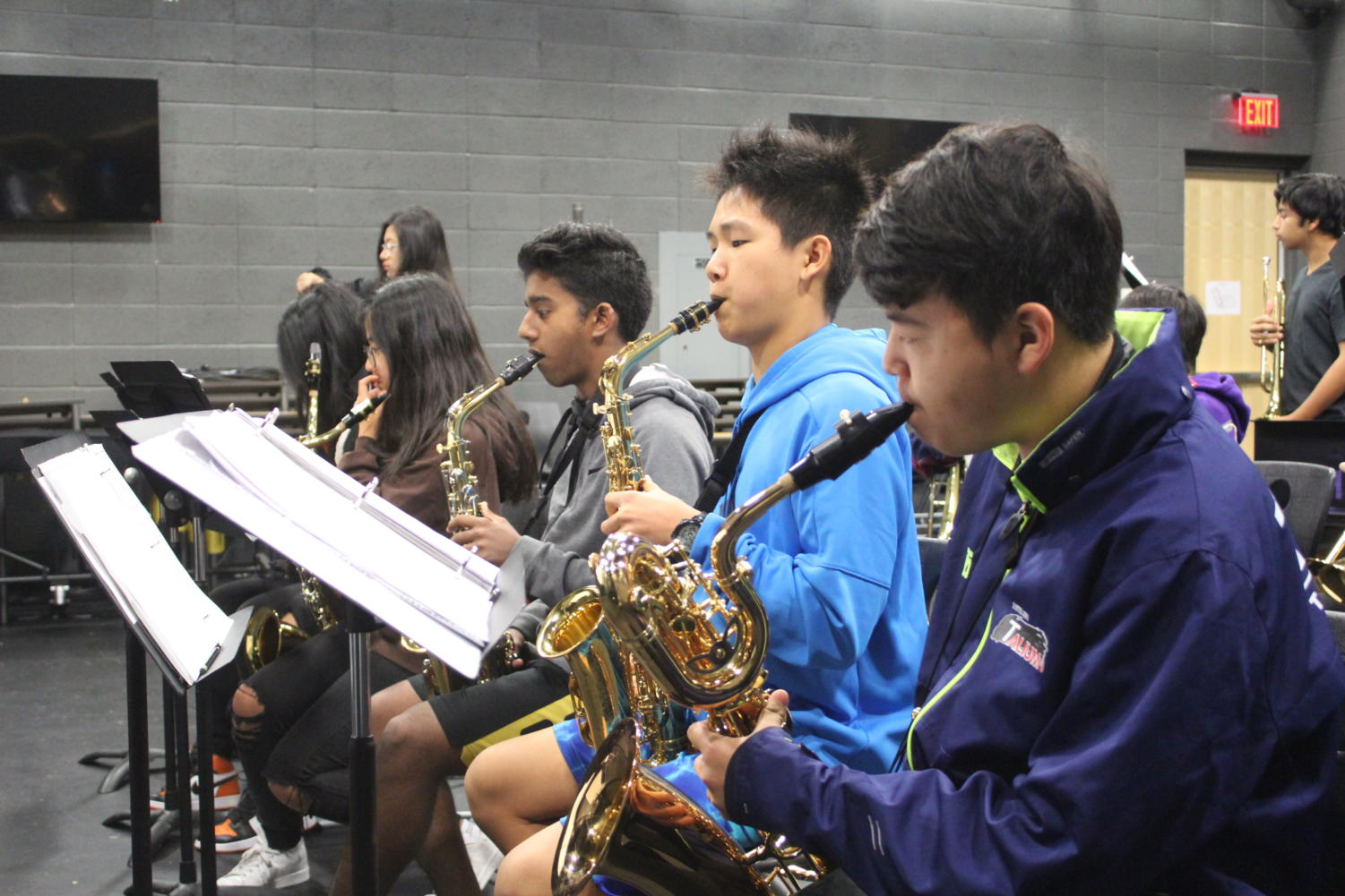 Within the front row of saxophones, alto saxophonists and sophomores Matthew Varughese and Kevin Du and baritone saxophonist freshman Garrett Lee play soulful blues during rehearsal in time with the rhythm and brass sections.