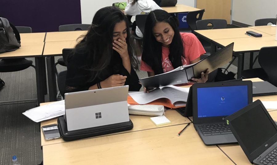 Junior+Mahum+Khan+and+sophomore+Lavanya+Gupta+observe+their+case+packets+to+try+to+come+up+with+strategies+which+will+enable+them+to+create+strong+arguments.