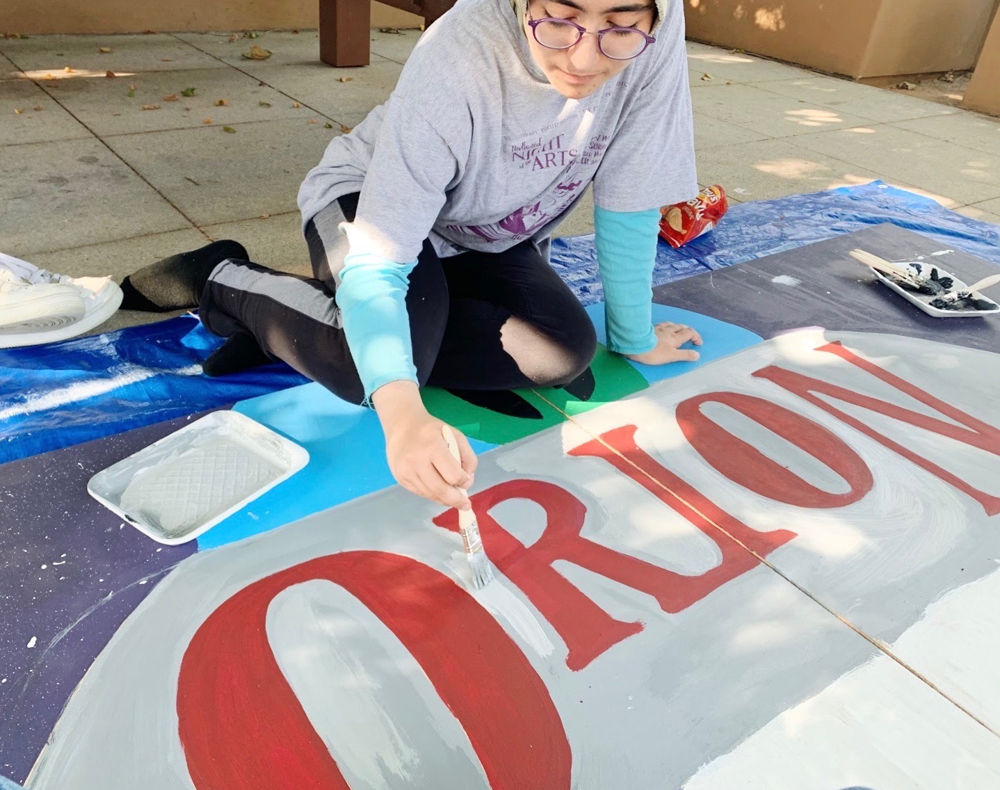 Junior Mona Tavassoli fills in the Orion backdrop. Students from all four houses gathered on Oct. 12 to paint backdrops and rehearse dances for the halftime show. ASB's efforts were more organized this year because of the increased participation and spirit of the student body.
