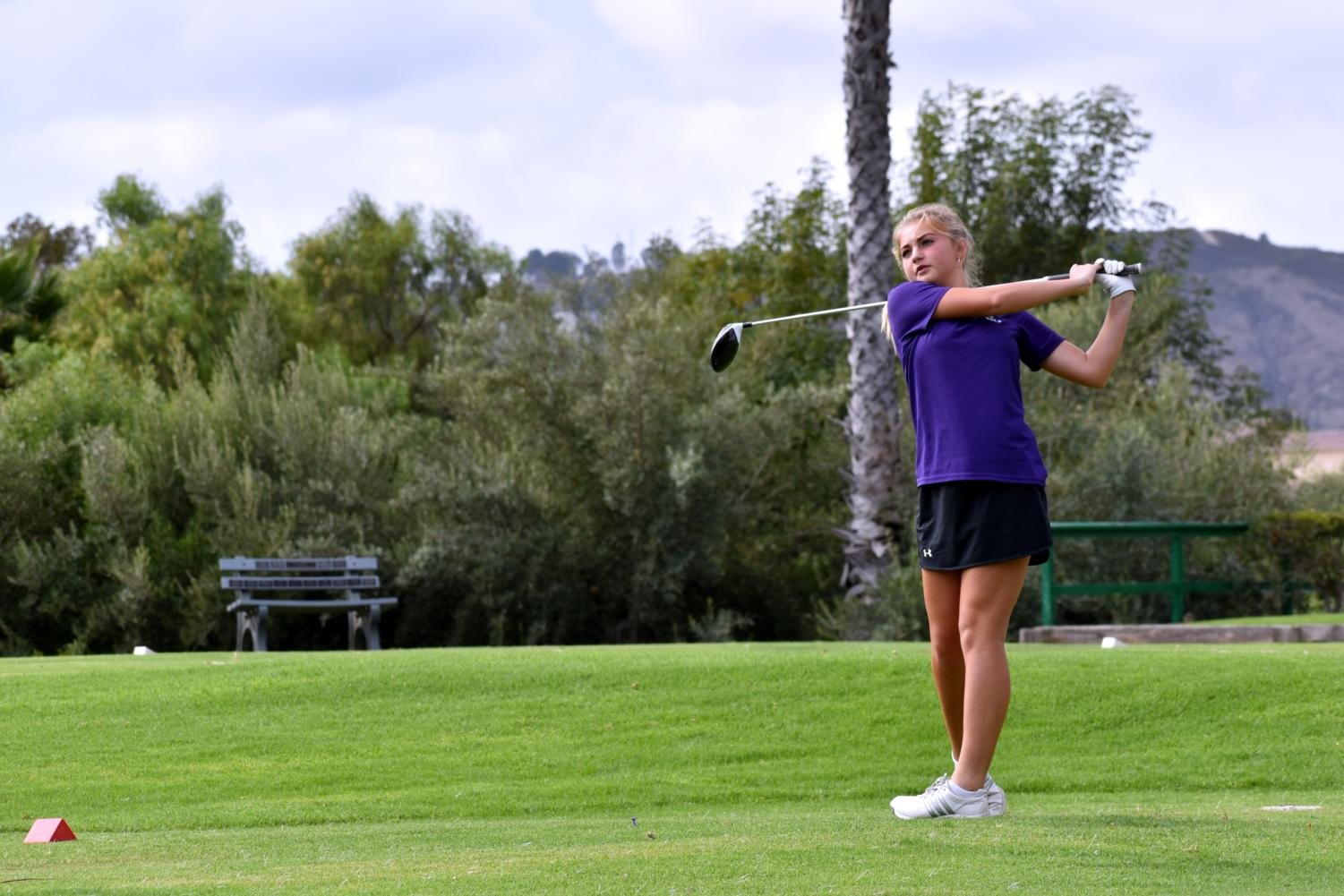 Sophomore and golfer Maddie Amlen rehearses her back swing at the first hole, preparing herself for a challenge throughout the match. Golfers on the high school level play nine holes in total, compared to the 18 that professionals play.