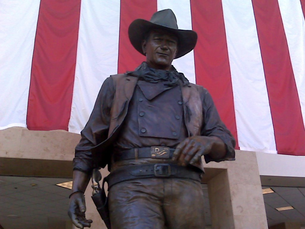 """A nine-foot bronze statue of John Wayne on a marble pedestal named """"The Duke"""" stands tall within John Wayne Airport, overlooking the Thomas F. Riley Terminal. Commissioned by the John Wayne Associates, sculptor Robert Summers created the statue to honor John Wayne and his patriotism."""
