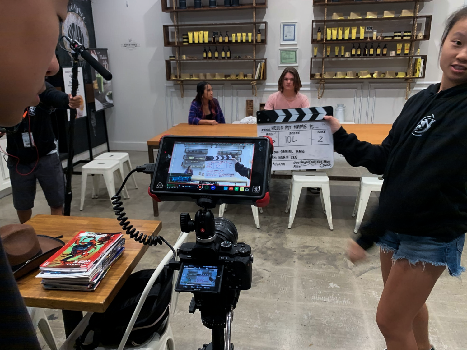 """Producer and junior Skye Lee positions the clapperboard in front of the camera to designate the scene on the set of the short film, """"Hello My Name Is."""" """"Hello My Name Is"""" is one of many entries from students being submitted to Orange County Film Festival this year."""