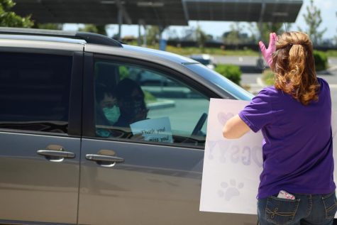 "Education specialist Desiree Shaffer waves a ""Go Bulldogs"" sign to incoming cars of students and family members, who show their appreciation even behind windows and masks. From a safe distance, Shaffer stops to check in and chat with the families before sending them down the line of other cheerful staff members."