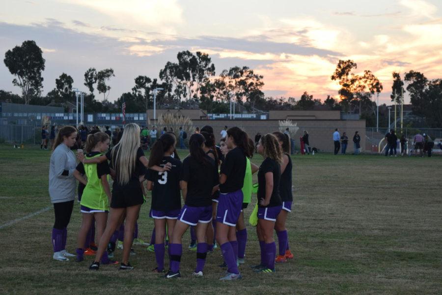 JV+Girls+Soccer+huddles+before+an+evening+matchup+against+University+High.