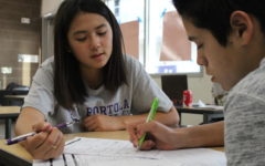 Peer tutor Lauren Hwang assists freshman Andre Quiroz with functions and other math topics during eighth period.