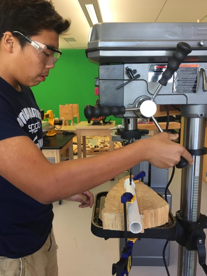Freshman Nick Hsu makes use of the machinery to drill a hole through a PVC pipe.