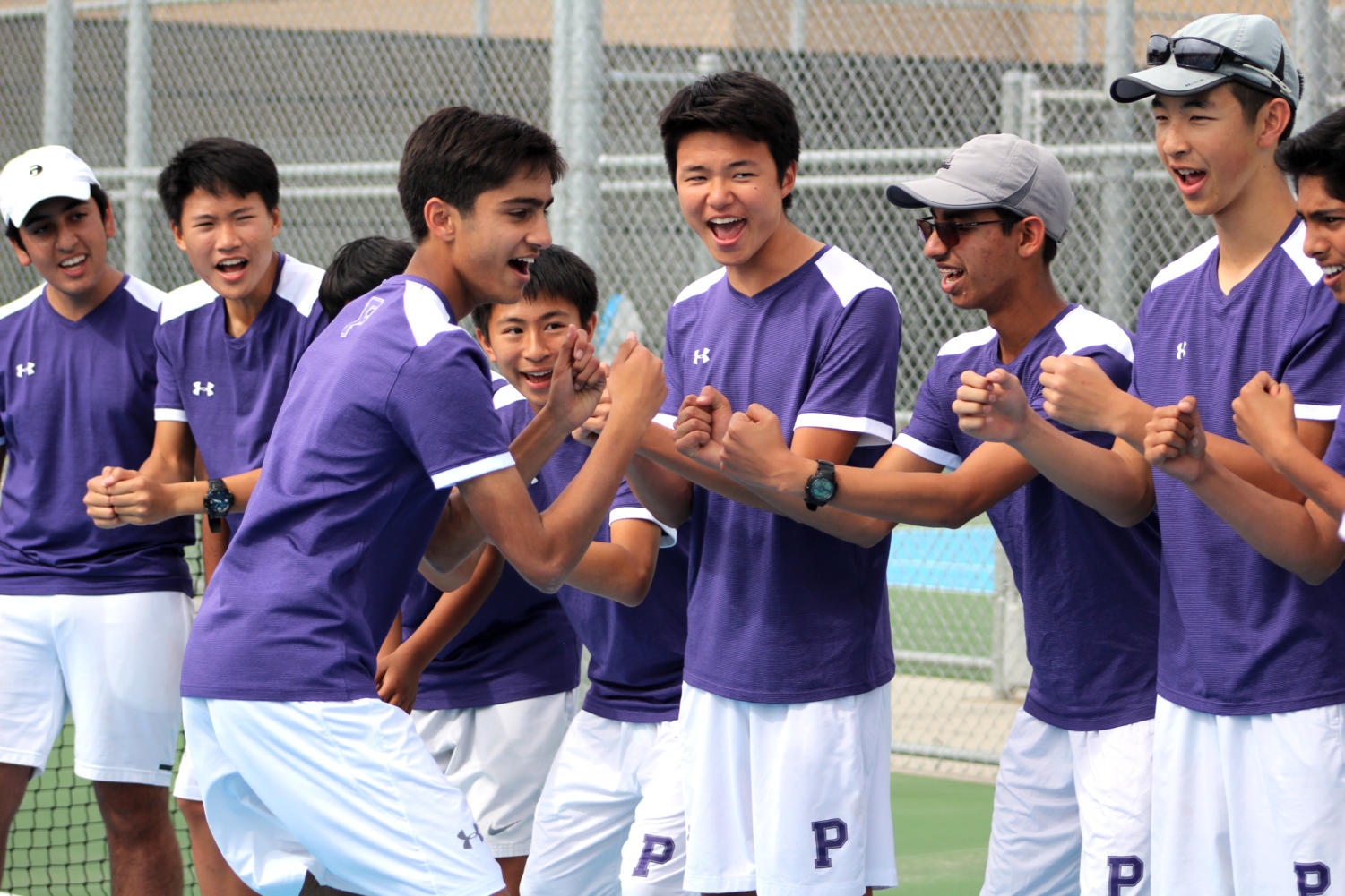 Sophomore Kameran Mody fist-bumps his team as he runs down the lineup at the start of the match in order to increase team spirit.
