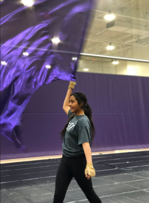 Freshman+Mahum+Khan+flourishes+her+swing+flag+to+the+side+before+starting+her+drill+during+winter+guard+practice.