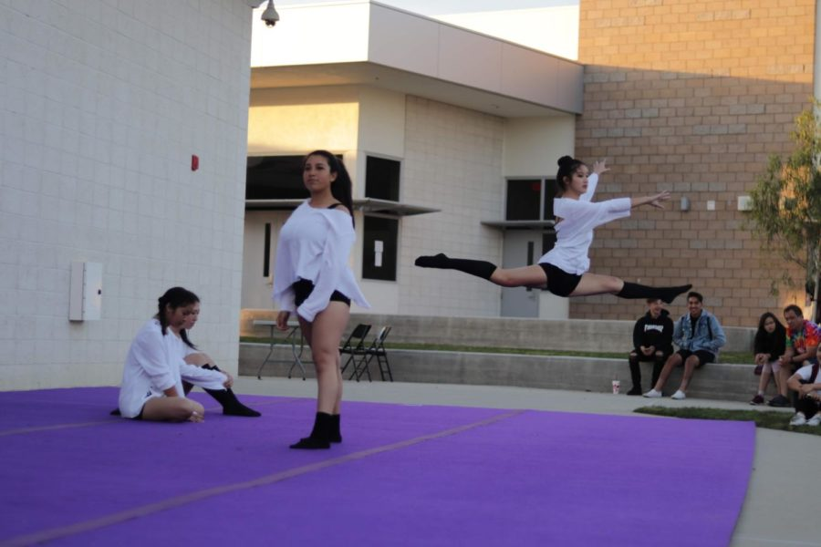 Sophomore+Alene+Hata+opens+up+the+dance+with+a+leap+as+Jaylin+Moreno+stands+from+her+opening+pose.+