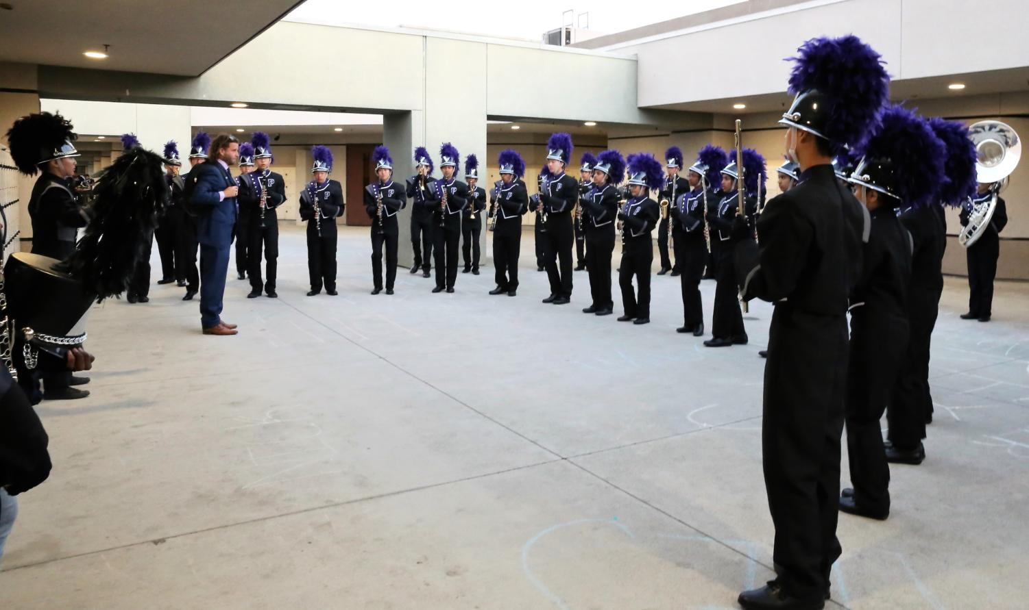 The marching band gets their final words of encouragement from teacher Desmond Stevens before embarking on their field show at the Tesoro Marching Band Field Tournament