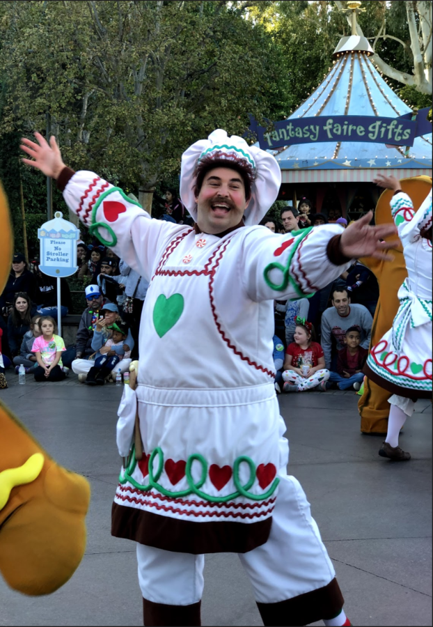 "Dressed as a baker accompanied by his fellow gingerbread men creations, this particular performer follows a parade float featuring a 6-foot tall book titled ""How to Make the Perfect Gingerbread House."""