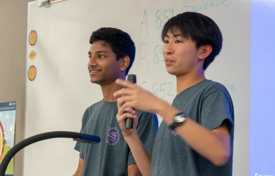 Junior Aditya Sasanur and sophomore Ethan Hung introduce the four stations planned for the event, including Math Bingo, Non-Newtonian Fluids, Aluminum Foil Boats and Artistic Points of Interest.