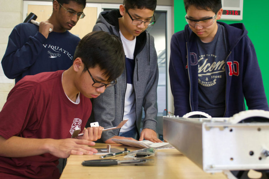 FIRST Robotic Team's sophomore Trung Huynh builds the structure for the battery compartment, finishing the final parts of the robot's base, while sophomore Neil Lin and freshmen Goshanraj Sandal and Ryan Bascos prepare for assistance. The robot is designed to secure the most game pieces possible into the rocket ship's holes in the time slot allowed, in a competition aligned with the 'Deep Space' theme.