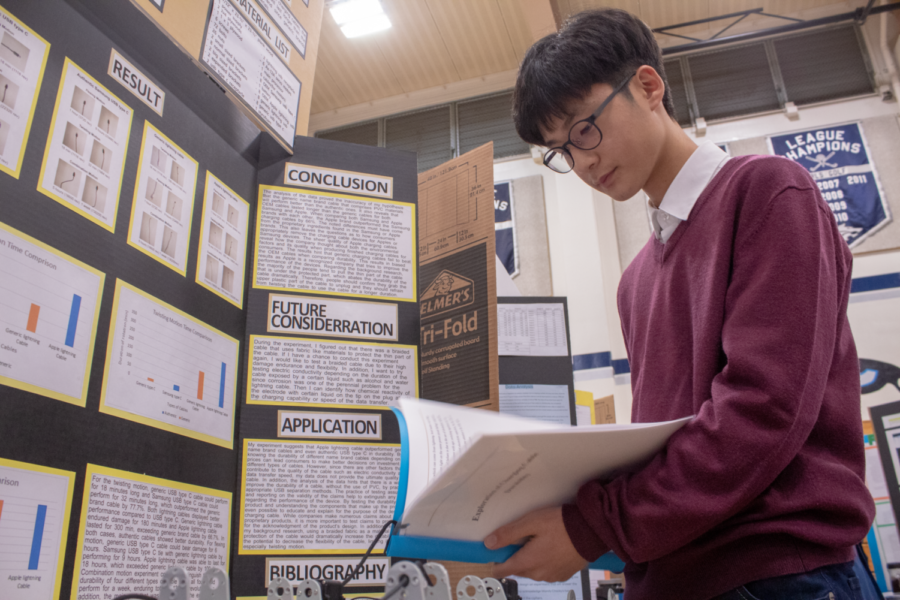 Sophomore and blue ribbon Physical Science winner Junho Park reviews his lab notebook detailing his experiment on the durability of charging cables.