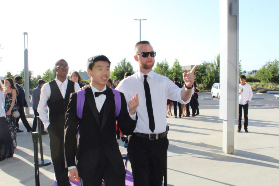 Junior and musician Caleb Ong poses with pit orchestra teacher Kyle Traska during their walk on the purple carpet.