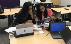 Junior Mahum Khan and sophomore Lavanya Gupta observe their case packets to try to come up with strategies which will enable them to create strong arguments.