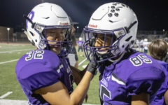 Juniors Dylan Chumm and Essa Khoso fix each other's chin straps and  tap helmets on the sidelines in preparation of yet another run out onto the field.