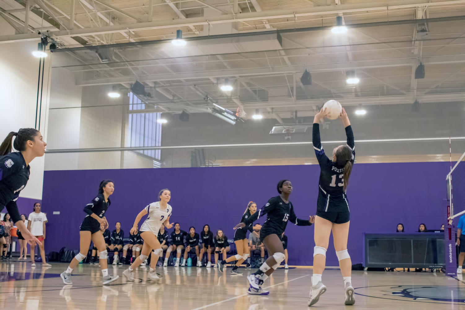 Junior and co-captain Faith DeNeve sets up a play for senior and middle blocker Arielle Hightower; the team has been focusing on setting up a kill through the middle during practices, but such plays require a nearly perfect pass and set, according to head coach Heidi Martasian.