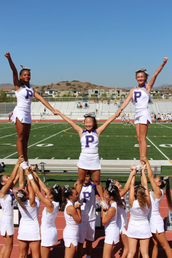 Freshmen side flyers Demetris Owens and Katelyn Toulmin stands next to sophomore center flyer Hailey Kim, in a stunt at a junior varsity football match against Laguna Hills High.