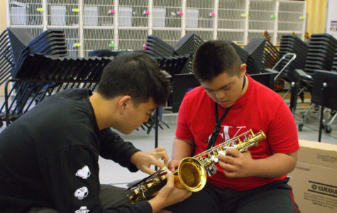 Sophomore and mentor Garrett Lee shows junior and mentee Justin Silva where to place his fingers on the saxophone. For beginner students like Silva, memorizing the location and placement of the many fingerings for the instrument can be difficult, which is why Lee must undergo training in the form of videos and books in order to be able to effectively teach his peers how to play.