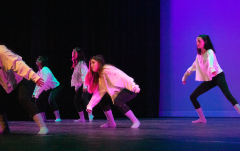 "Dance 3 students crouch down during the solo section of the piece, ""Crybaby,"" choreographed by sophomore Mia Zappala. Choreographers were also responsible for costume design and stage lighting, fine-tuning these elements to enhance their overall performance."