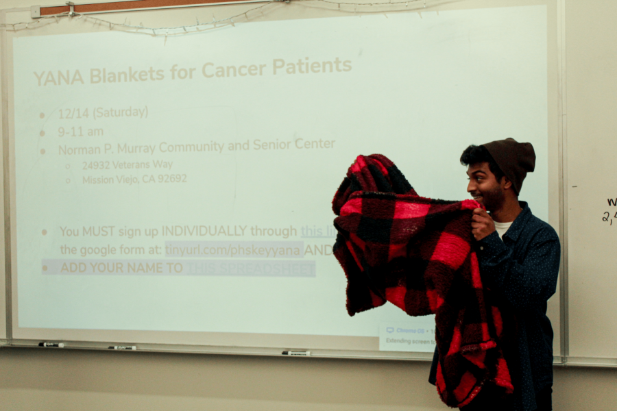 Club+technology+adviser+and+junior+Ashwin+Kunaseelan+demonstrates+how+members+will+make+blankets+for+cancer+patients+with+other+high+school+Key+Clubs+at+a+brand+new+volunteer+event.