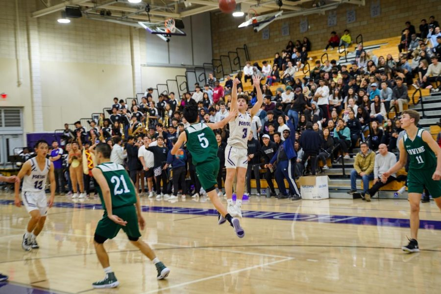 Guard and senior Robert Giraldy launches a three pointer from the deep despite heavy defense from Irvine High.