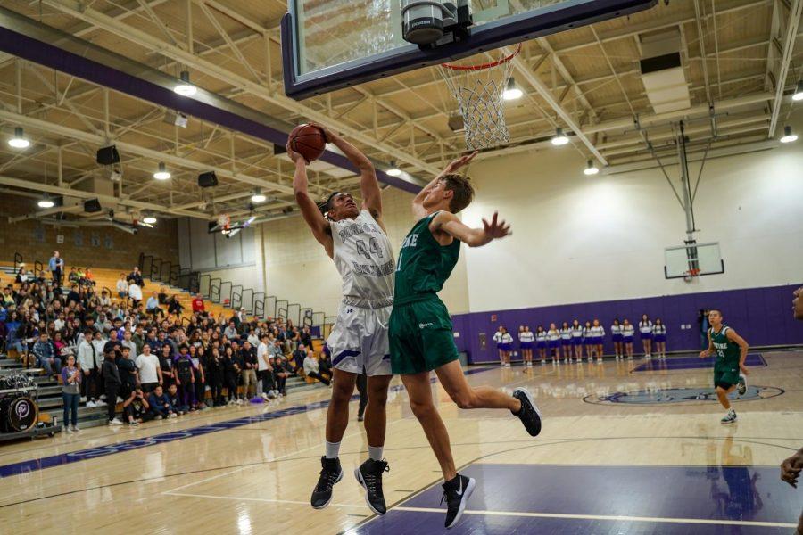 Center and senior Jared VanHaeren reaches over an Irvine High defender to make a layup.