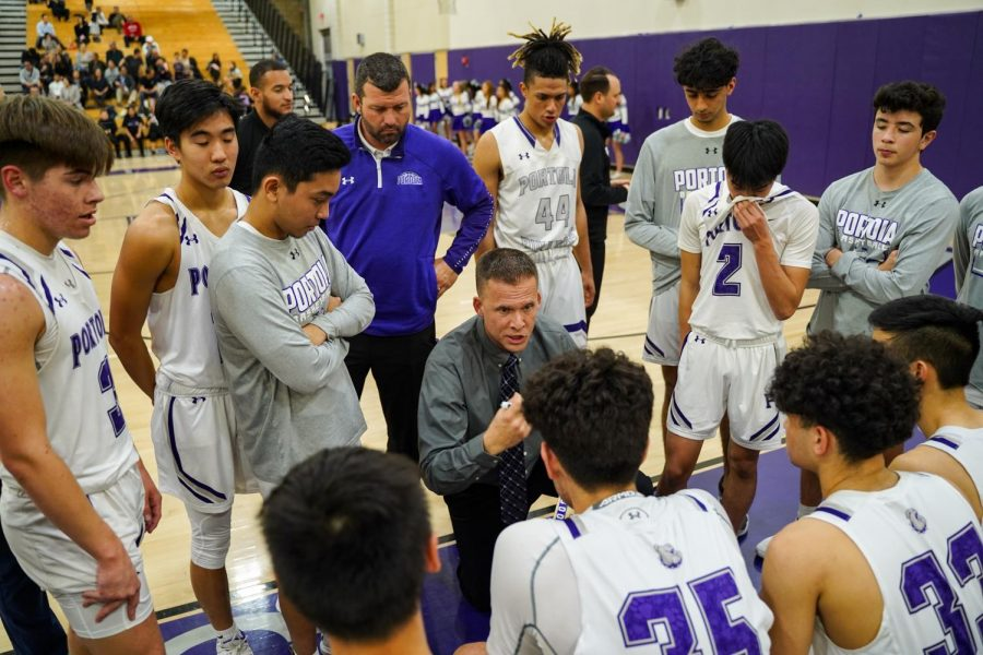 Head coach Brian Smith explains a new offensive play to his players during a timeout.