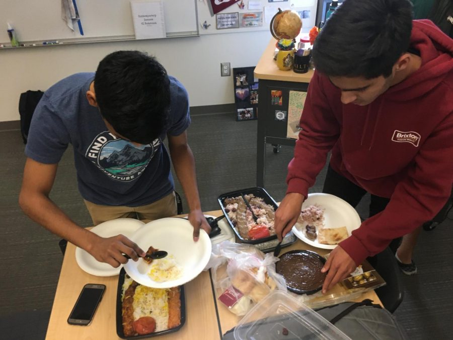 Club president and senior Kameran Mody and club member and senior Aditya Sasanur serve some Persian dishes. Made by speaker and senior Shawyan Rooein, he brought a chicken koobideh and a beef koobideh dish, which is composed of ground chicken/beef mixed with spices and onion and grilled on a skewer.