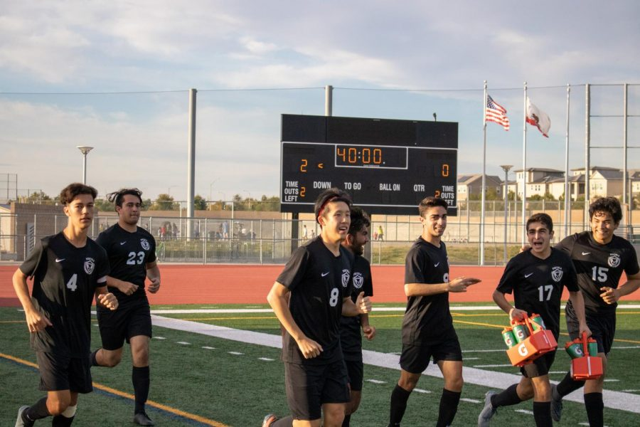 The boys' team takes the field, excited to start the second half on their way to a commanding 3-0 victory.