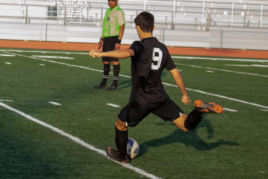 Junior Sherwin Salehi takes a free kick, one of several in a chippy game for both sides.