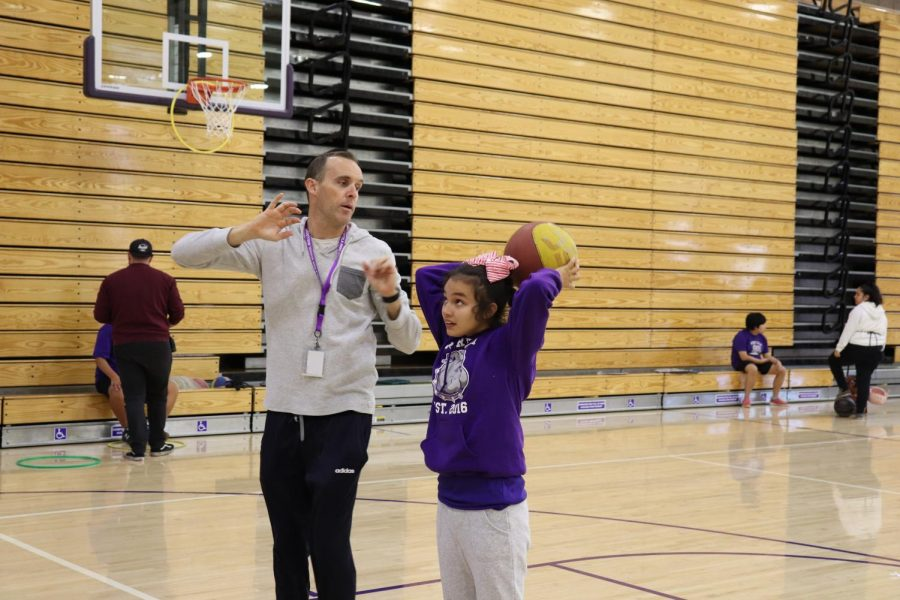 Freshman Molly Lamon-Paredes practices in the gym during her physical education period. Adaptive PE teacher Erie Eastman closely assists students to teach correct form and helps ensure each student enjoys the activity.
