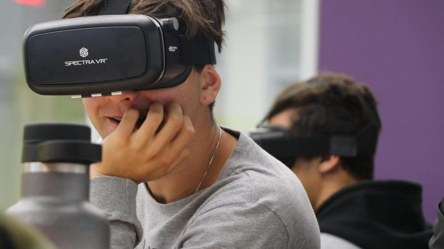 Senior Victor Loyola smiles as he explores different environments through the VR headset without leaving his seat. Among 8-to-17-year-olds who own virtual reality technology, 33% use the device for exploring environments, while 22% use it to learn something, according to a survey by Common Sense Media.