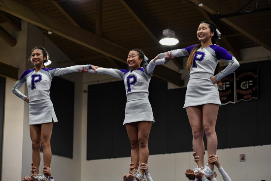 Senior Jessalyn Nguyen, sophomore Hailey Kim and junior Elisa Tan link arms in a stunt at the regional competition. Each cheerleader receives specialized training specific to their role in the routine, and all must work together closely to make the performance possible.