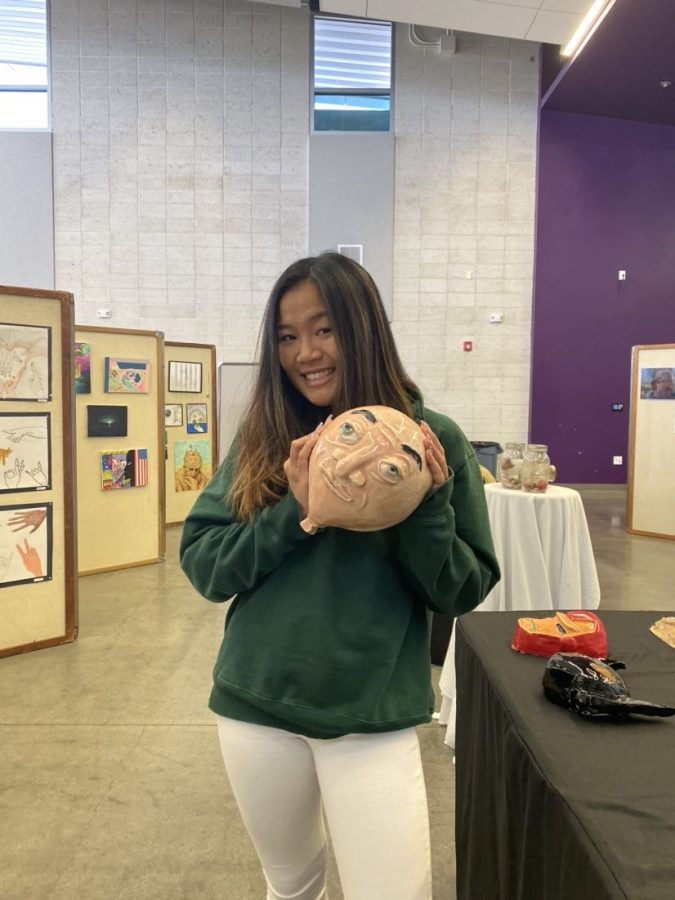 "Junior Kayla Nguyen presents her ceramics creation of ""Balloony,"" inspired by the television show ""Phineas and Ferb,"" at Fine Arts Week."