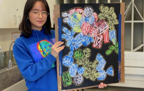 Junior Esther Moon explores the topic of material wealth and its value in society using a printmaking piece with gold acrylic paint embellishments.