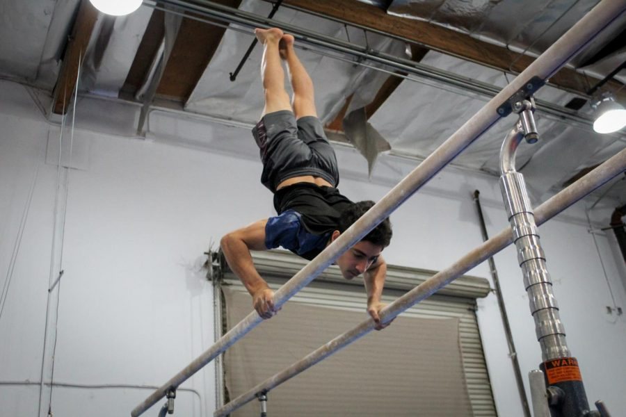 Sophomore+Kian+Miremadi+maintains+a+handstand+during+his+swing+on+parallel+bars.+The+drill+combines+aspects+of+strength+and+balance%2C+requiring+the+gymnast+to+have+upper-body+control.