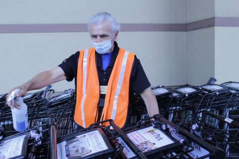 A Ralphs employee, Marko, sanitizes carts to ensure the safety of customers. While Ralphs still maintains its normal operating hours as they are necessary for providing residents food and day-to-day essentials, they have implemented precautions that reduce risk of customers contracting the virus.