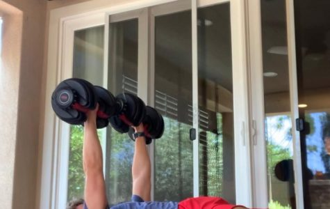 Water polo player and sophomore Andrew Cherry does his workouts in his backyard after a run, and usually lifts weights to make sure his arms will be toned in condition when school starts again.