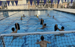 Boys water polo athletes conduct a shooting drill with sanitized kickboards and gloves to minimize contact with the ball.