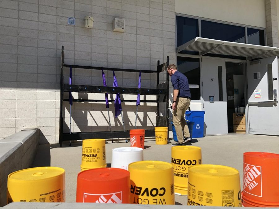 As a precaution against COVID-19, instrumental music teacher Kyle Traska sprays a series of bucket drums with cleaning solvent after a Wind Ensemble rehearsal. With one assigned to each student, the buckets offer unique flexibility in both maintenance and curriculum.