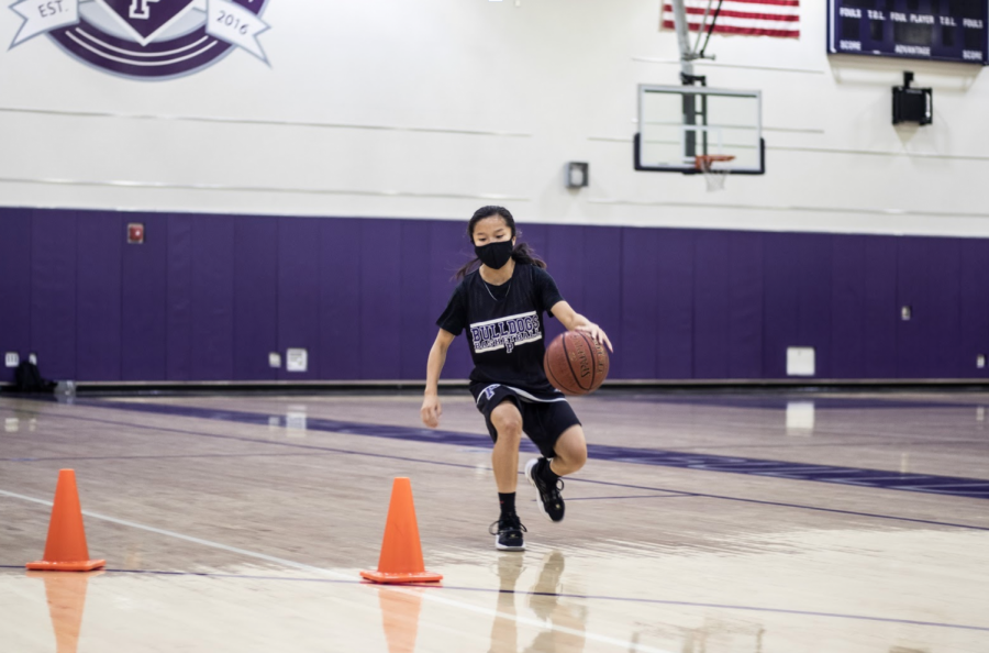 "Under COVID-19 precautions, varsity basketball player and freshman Kira Watanabe spends her first year unable to pass balls and play as a team during practice. ""We lost summer programming; we lost fall programming,"" Brian Barham said. ""High school basketball is an adjustment, and it"