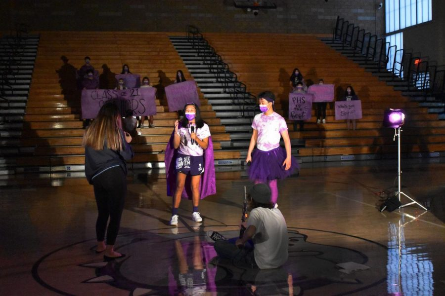 Spirit and rally commissioners senior Kai Wong and junior Ryan Jung address the school as junior Tiffany Park holds her camera. The throwback-themed rally is meant to remind students of the gym as it would have been during an in-person rally.