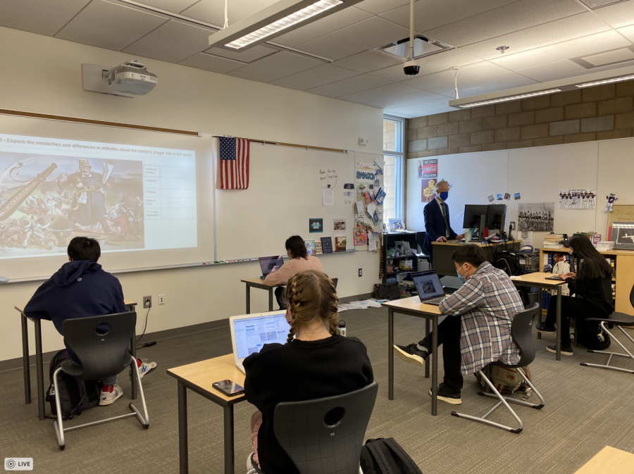 AP U.S. History teacher Wind Ralston prepares his students for their online AP exam by practicing analyzing a political cartoon. AP U.S. History is one of the classes that includes all units from the curriculum and will not exclude any units due to the pandemic.