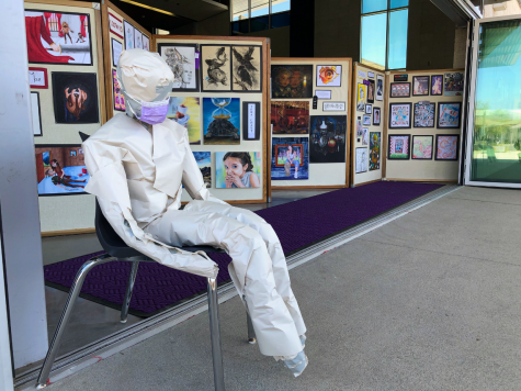 A masked figure made from packing paper by senior Ashley Pyun sits at the front of the Media Center art gallery, designed to show respect for all of the first responders who worked during the COVID-19 pandemic. Students in Honors Modern Contemporary Art designed various installations individually and in groups, and the classs top three favorites were put on display, according to art teacher Kearci Moir.