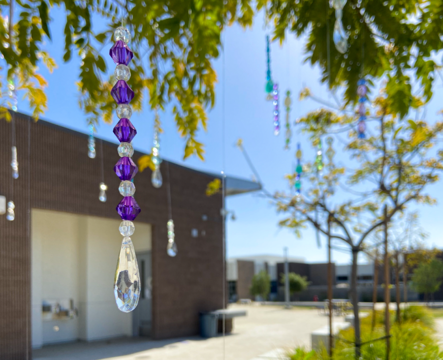 Outside the art room, beads of various colors hang from trees and reflect the sunlight. Senior Rue Coskun prepared the installation using beads she found and upcycled. The dangling art pieces were set up on April 5, the first day of Fine Arts Week.